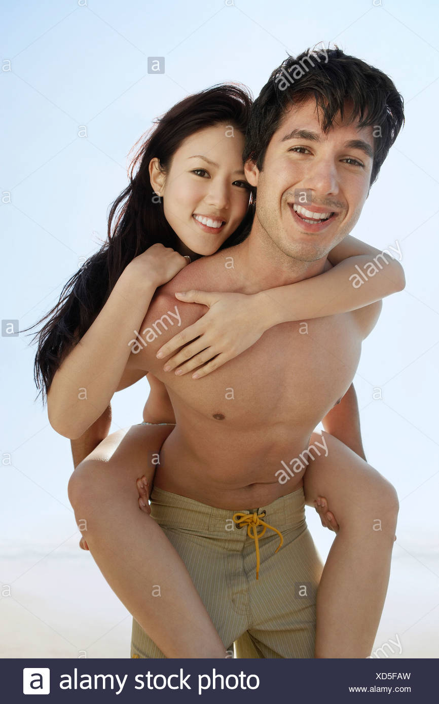 Young woman riding on man's back, portrait - Stock Image