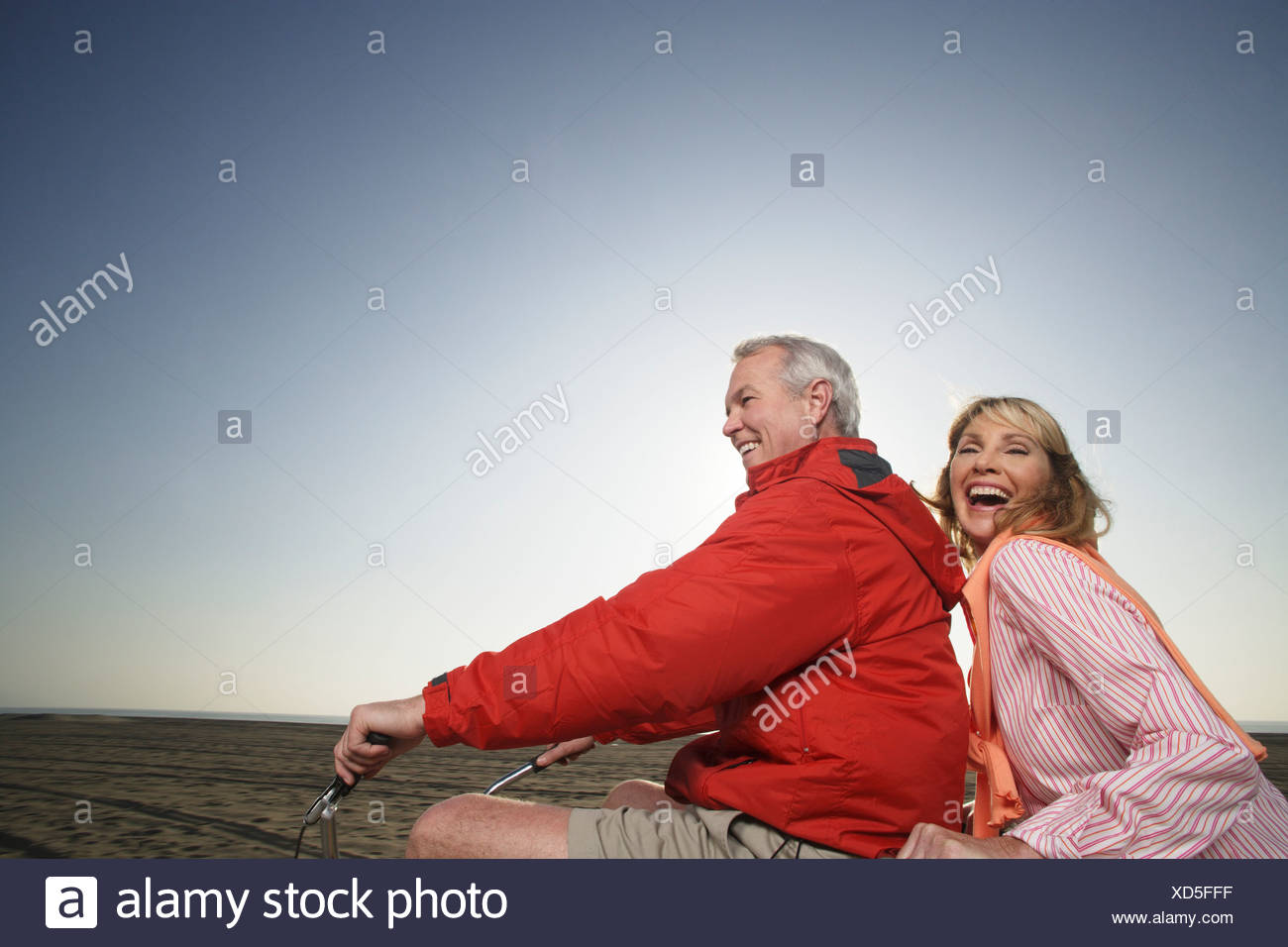 mature couple riding tandem bike on the beach stock photo: 283478371