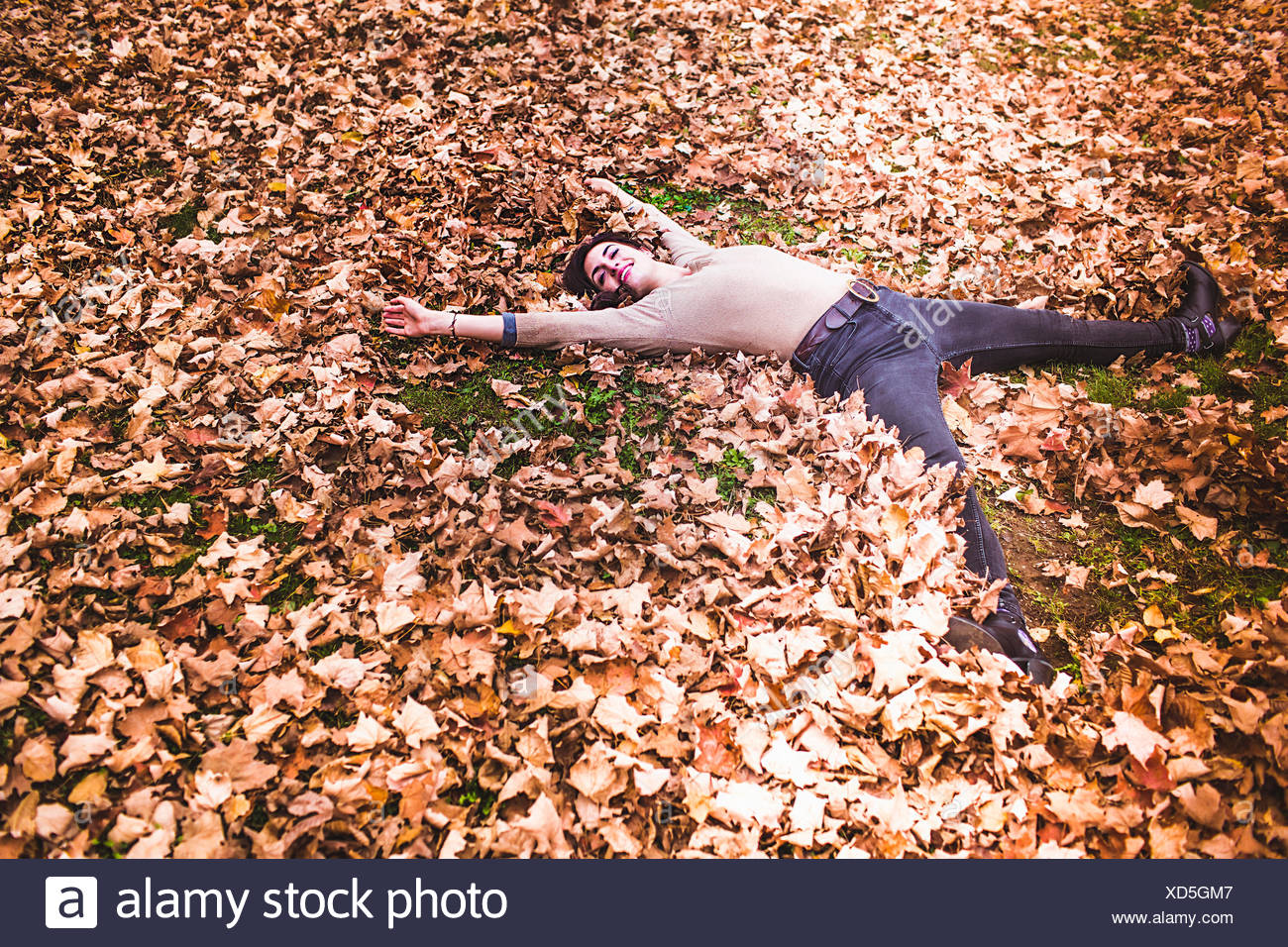 Overhead view of young woman lying on autumn leaves with arms and legs outstretched - Stock Image