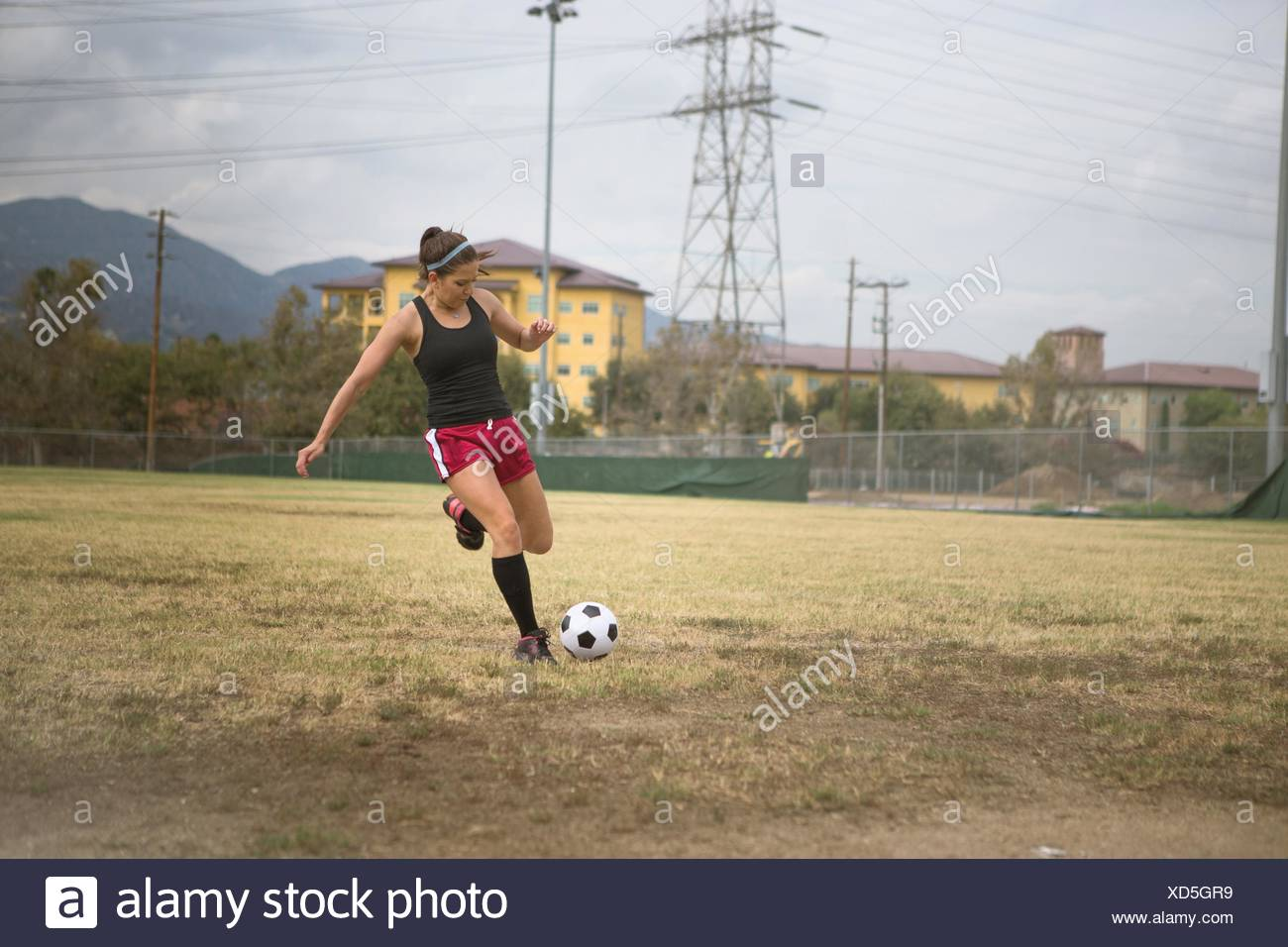Soccer player practising in field - Stock Image