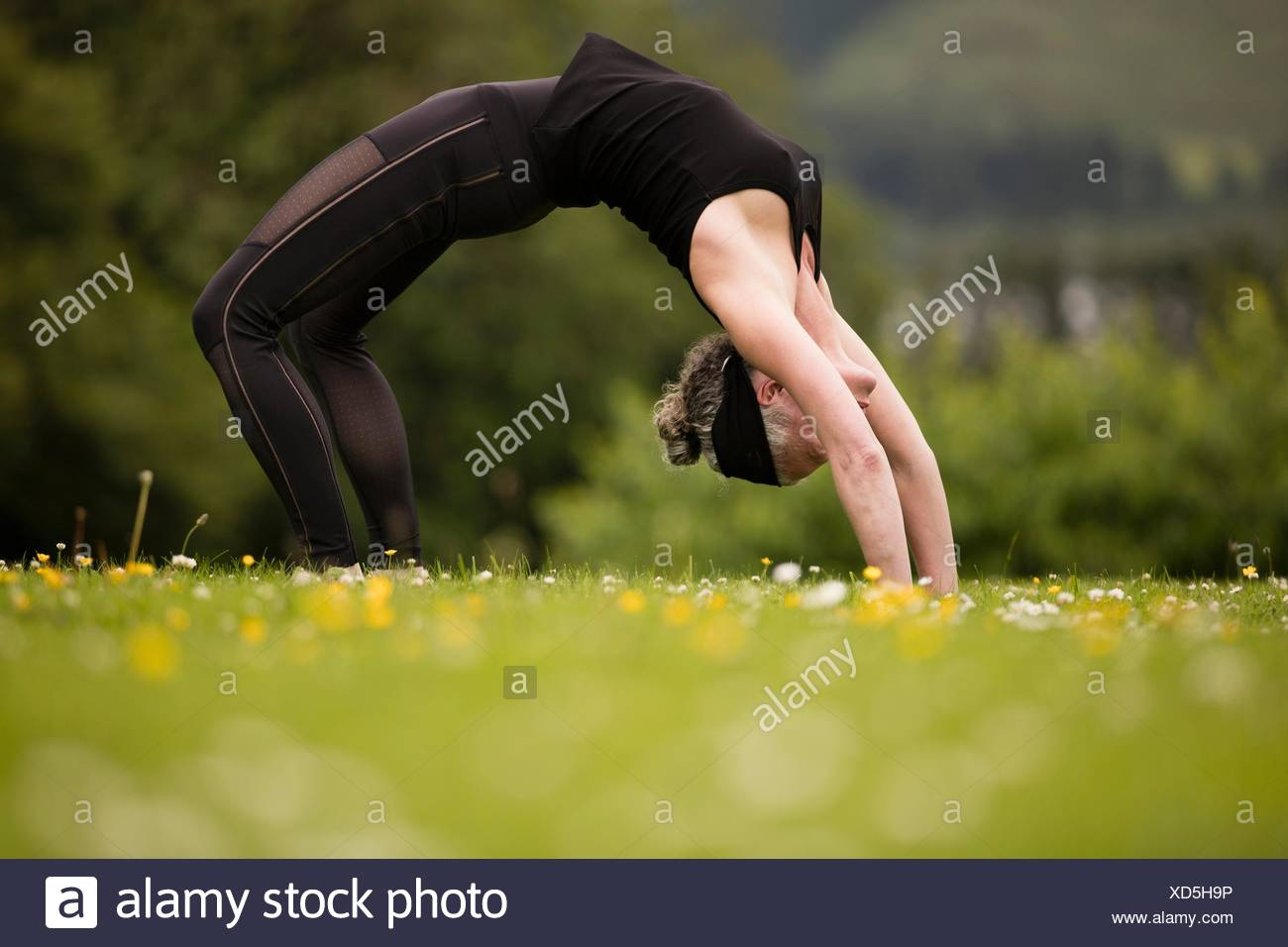 Mature woman practicing yoga backward bends in field - Stock Image