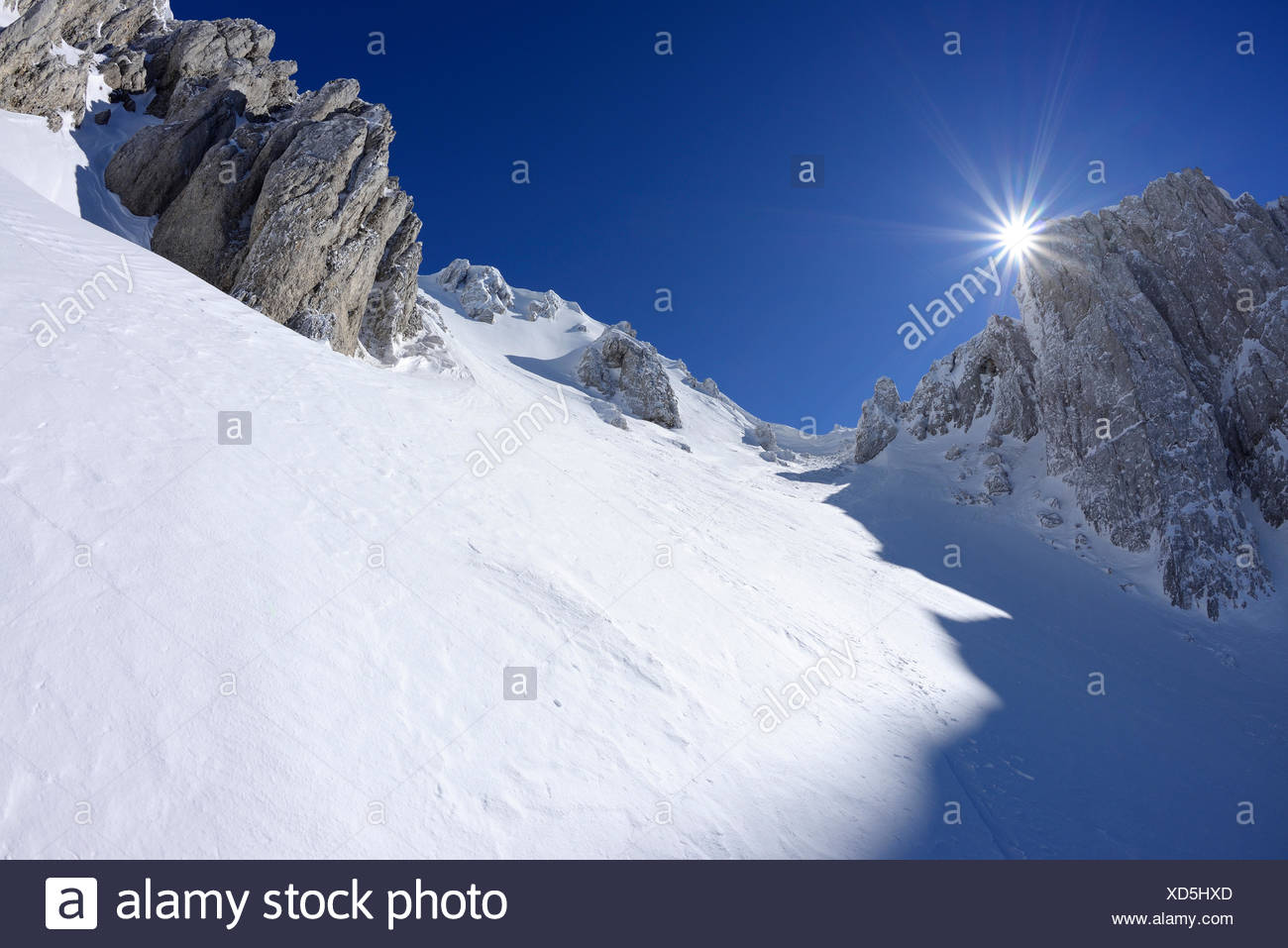 Sun gleaming over the snow-covered cirque at Monte Sirente, Valle Lupara, Monte Sirente, Abruzzi, Apennines, l' Aquila, Italy - Stock Image