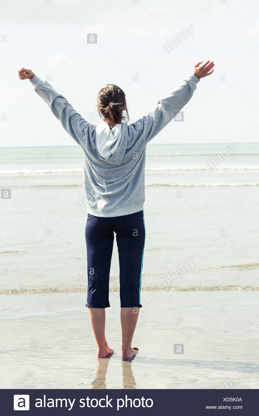 Woman opening her arms in front of the sea - Stock Image