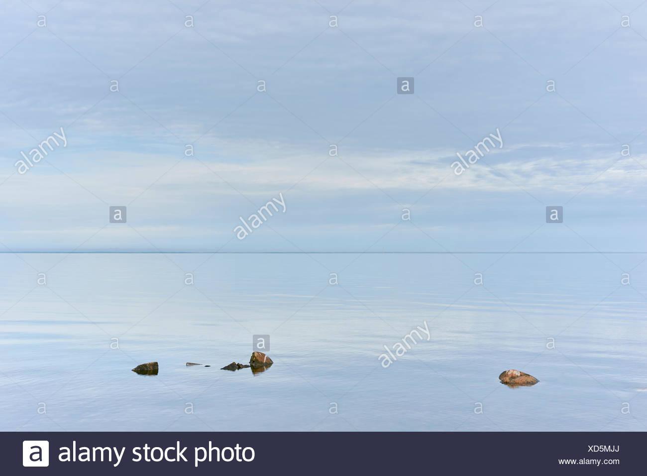 Rocks protruding from still sea, Aland, Kalmar, Sweden - Stock Image