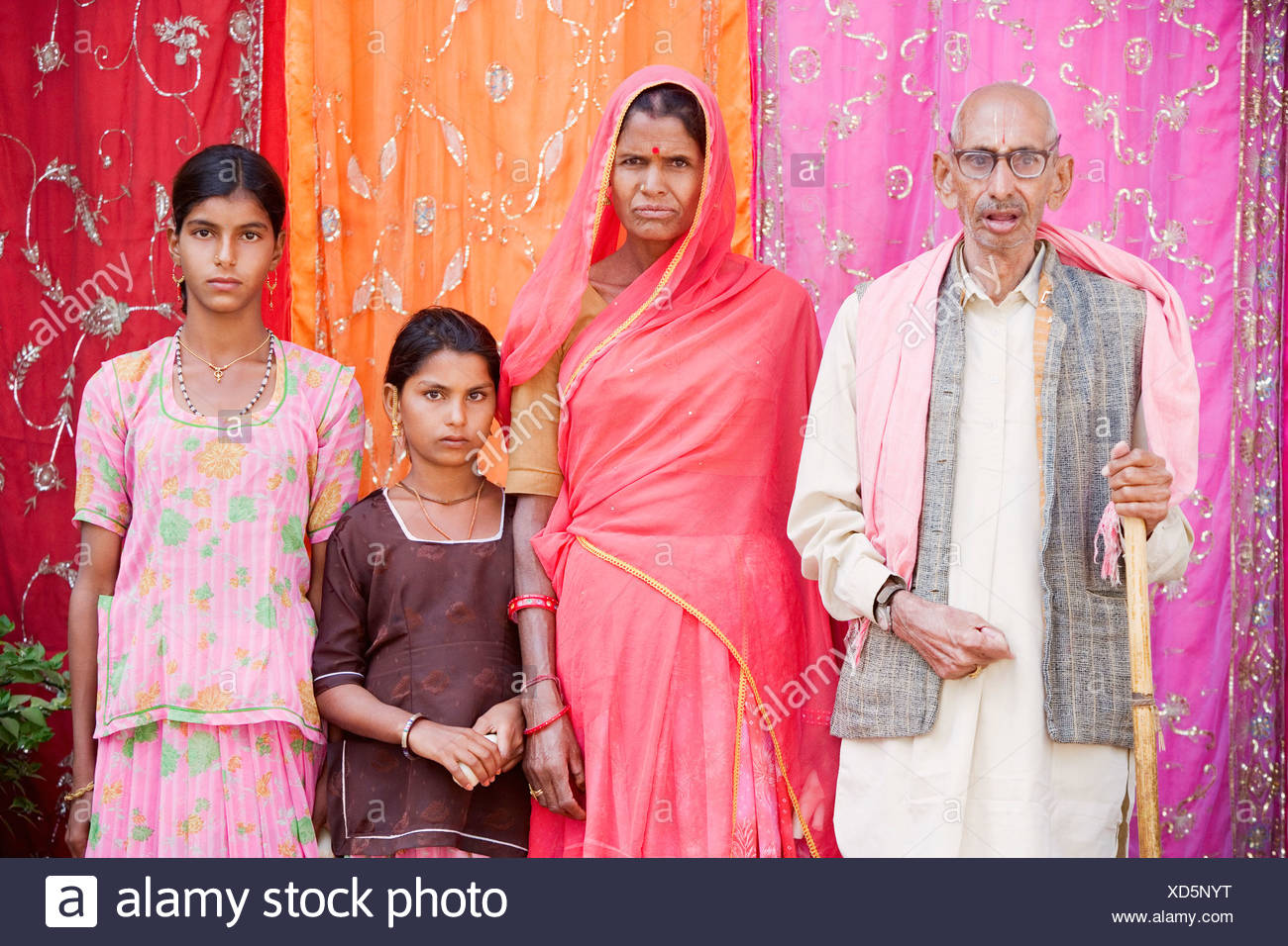 Senior man and a mature woman standing with their two granddaughters - Stock Image