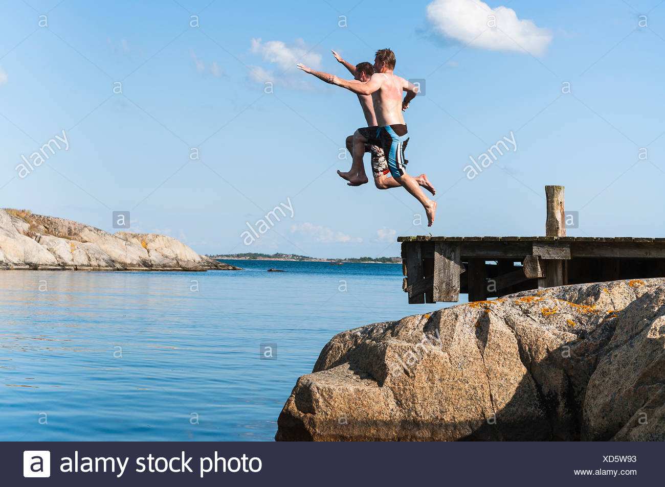 Sweden, Stockholm archipelago, Uppland, Vidinge, Two men jumping into lake from jetty - Stock Image