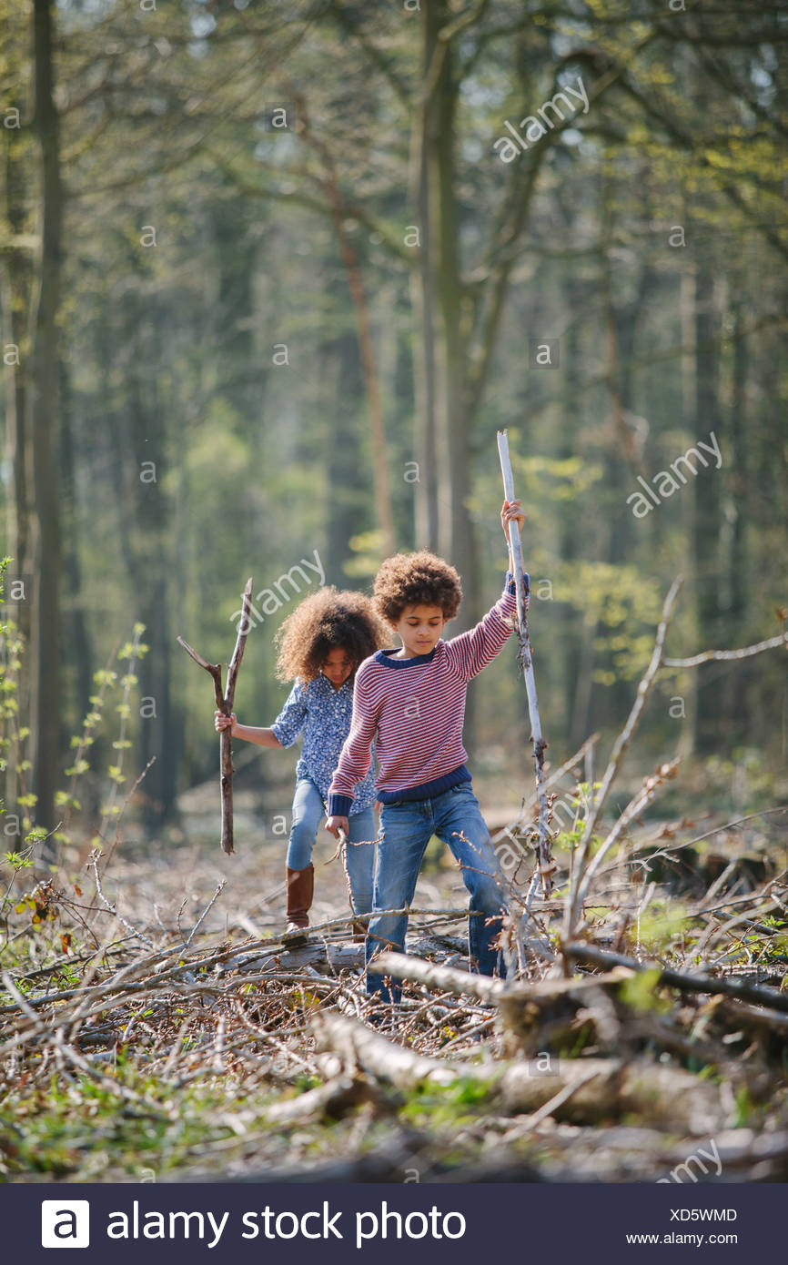 Brother and sister exploring together in woods Stock Photo