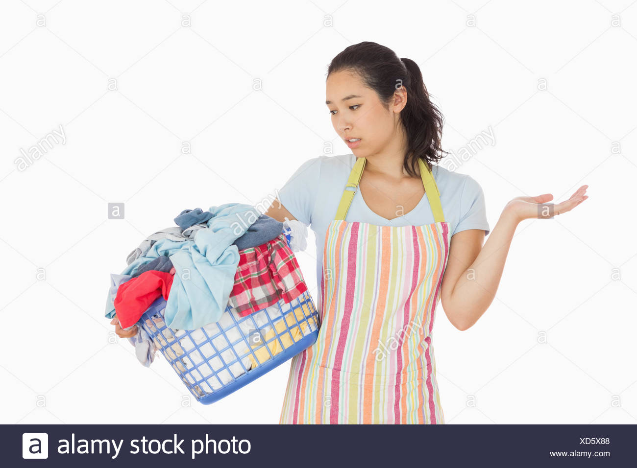 Quizzical looking young woman looking at basket - Stock Image