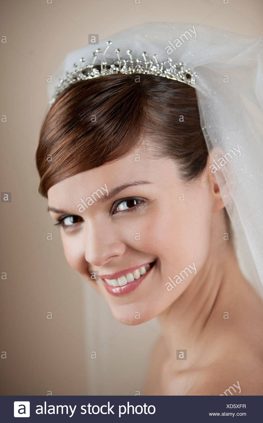 A young bride wearing a tiara and veil, smiling Stock Photo