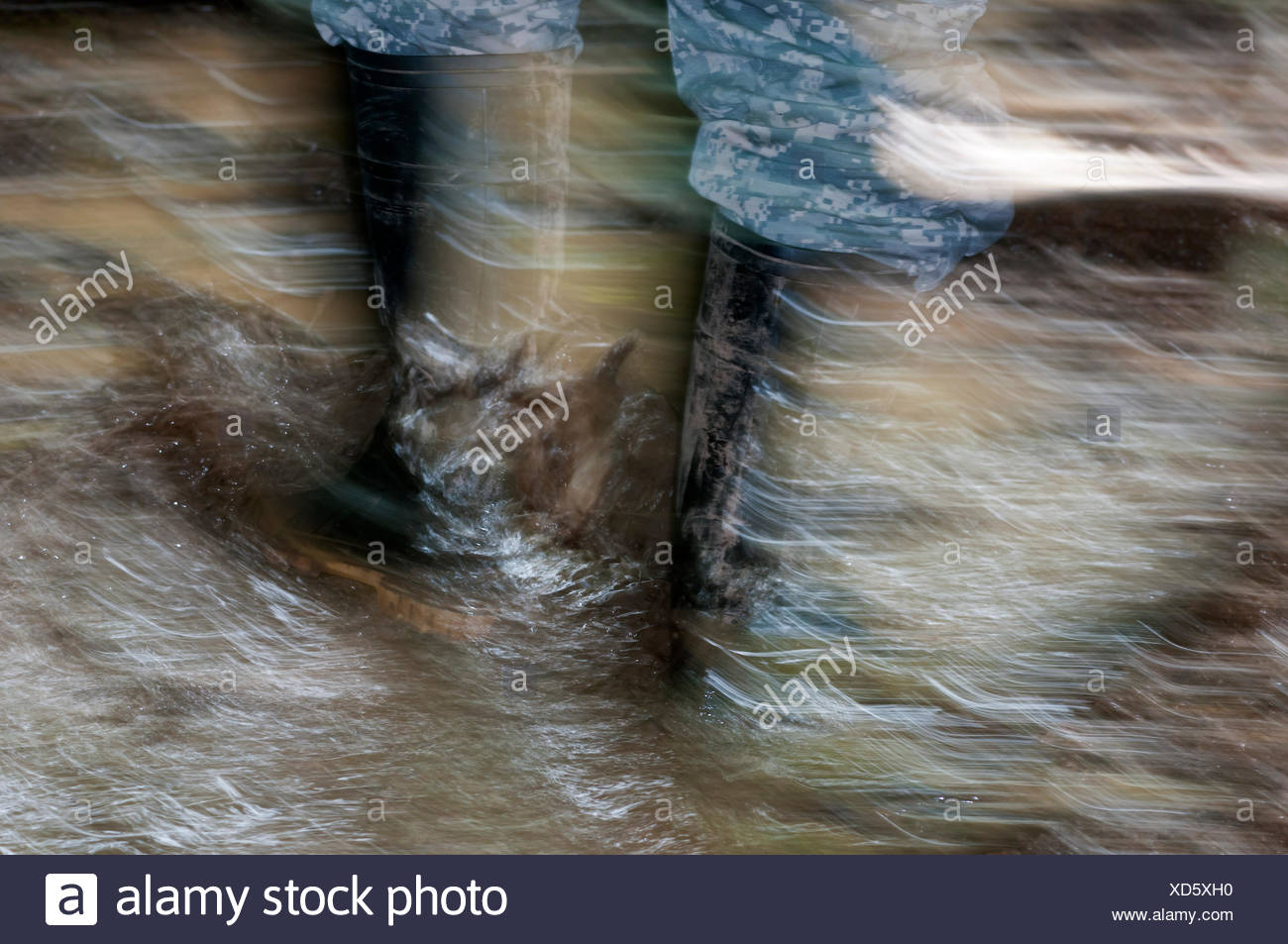 Walking with rubber boots in muddy terrain, Tambopata Nature Reserve, Madre de Dios Region, Peru - Stock Image