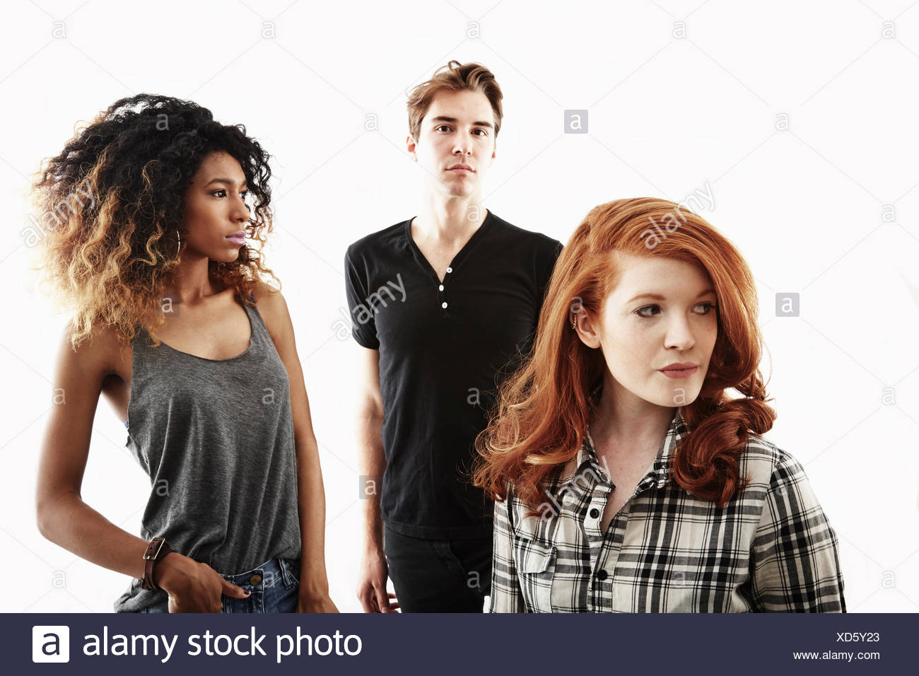 Studio portrait of two young adult women and one young adult man - Stock Image