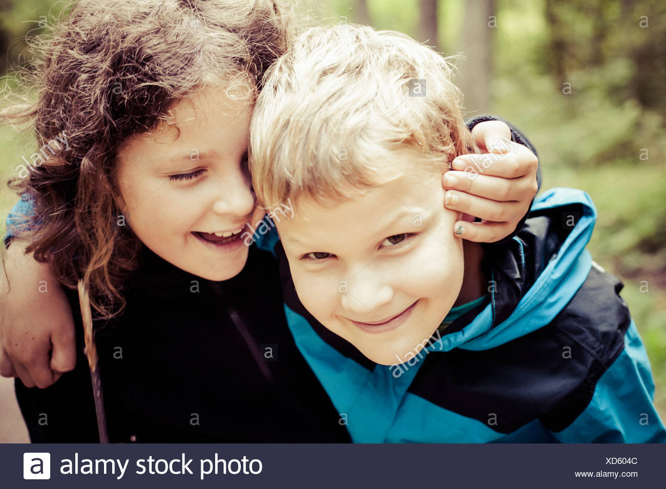 Young girl whispering into brother's ear outdoors - Stock Image