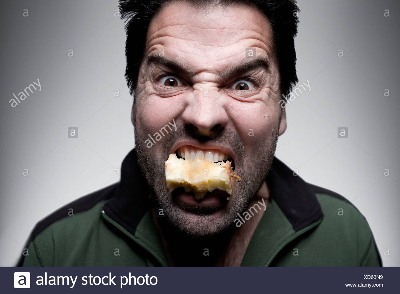 A man holds an apple core in his mouth, San Diego, California. - Stock Image