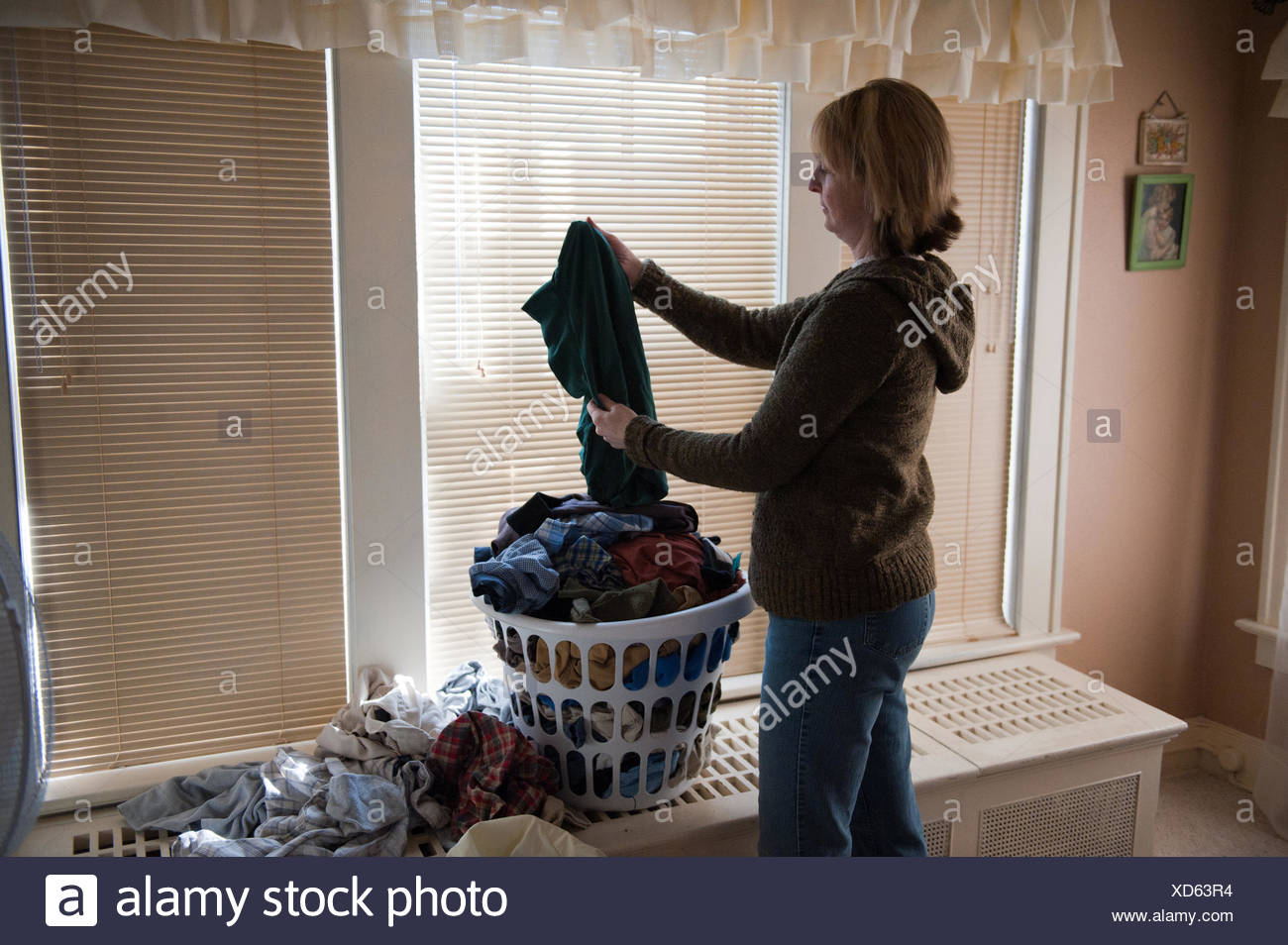 A woman folds laundry at her home in Lincoln, Nebraska. - Stock Image