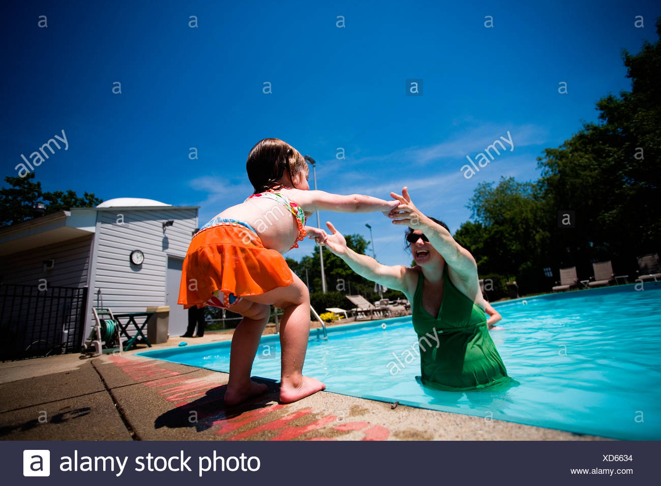 A small girl reaches for mom in the pool. - Stock Image
