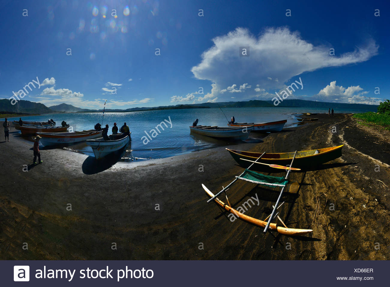 Local fishermen on the beach and an outrigger canoe. - Stock Image