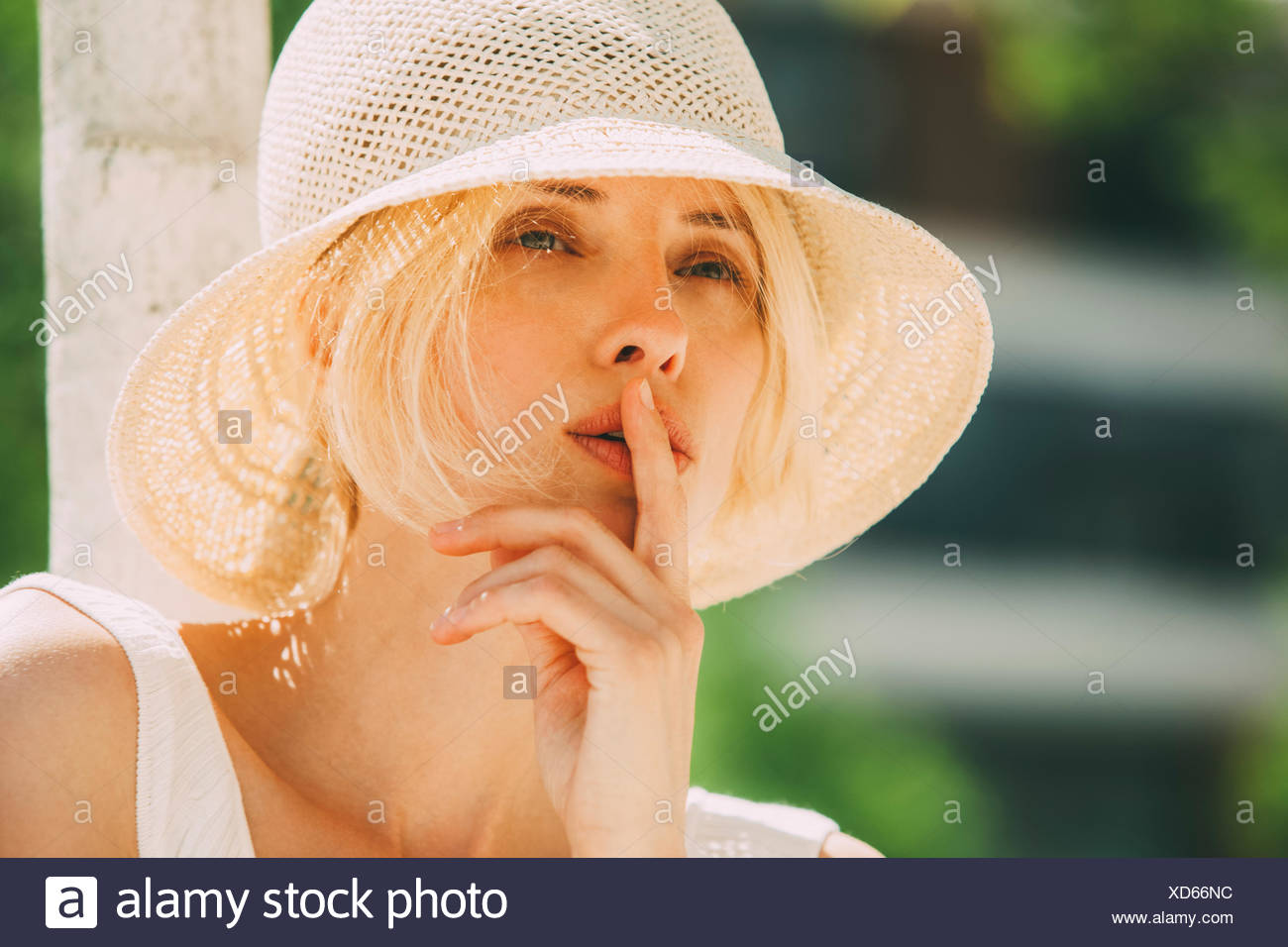 Portrait of blond woman wearing summer hat - Stock Image