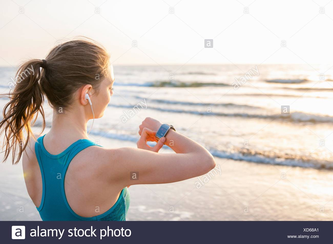 Over the shoulder view of mid adult woman by ocean wearing earbuds looking at wrist watch - Stock Image