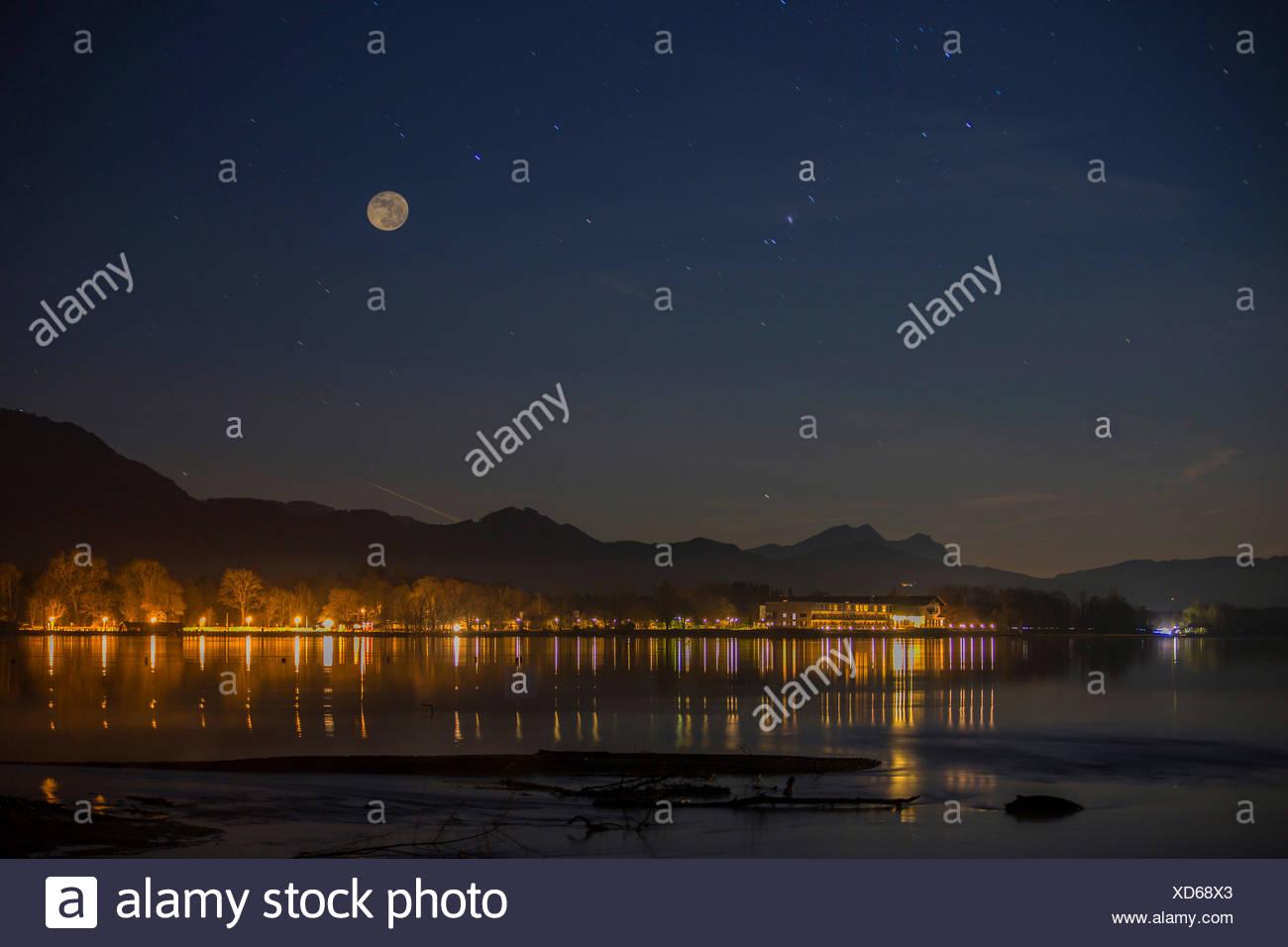 Vollmond ueber dem Chiemsee, Beleuchtung von Strasse und Gebaeuden spiegelt sich im See , Deutschland, Bayern, Chiemsee   illumi - Stock Image