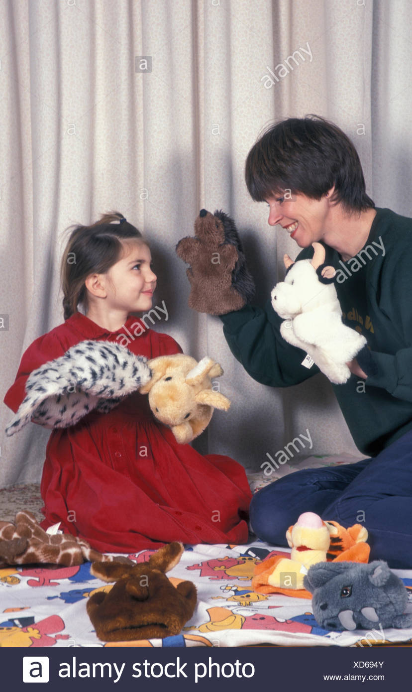 woman playing puppets with girl - Stock Image