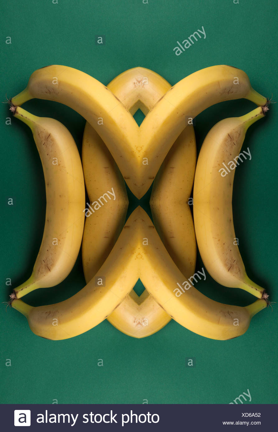 A digital composite of mirrored images of an arrangement of bananas - Stock Image
