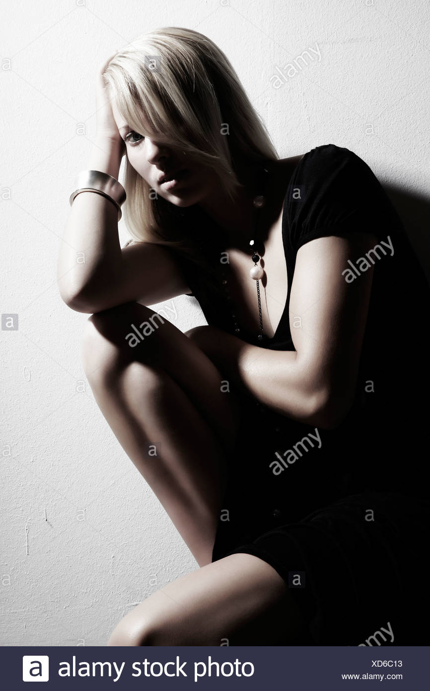 Portrait of a young woman wearing a black dress crouched thoughtfully against a wall and looking towards the viewer - Stock Image