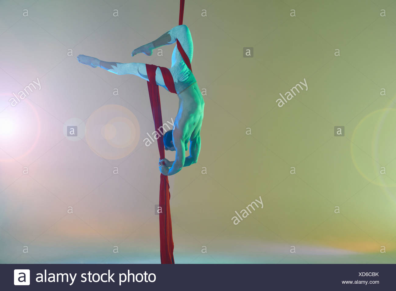 Aerial dancer with red ribbon upside down - Stock Image