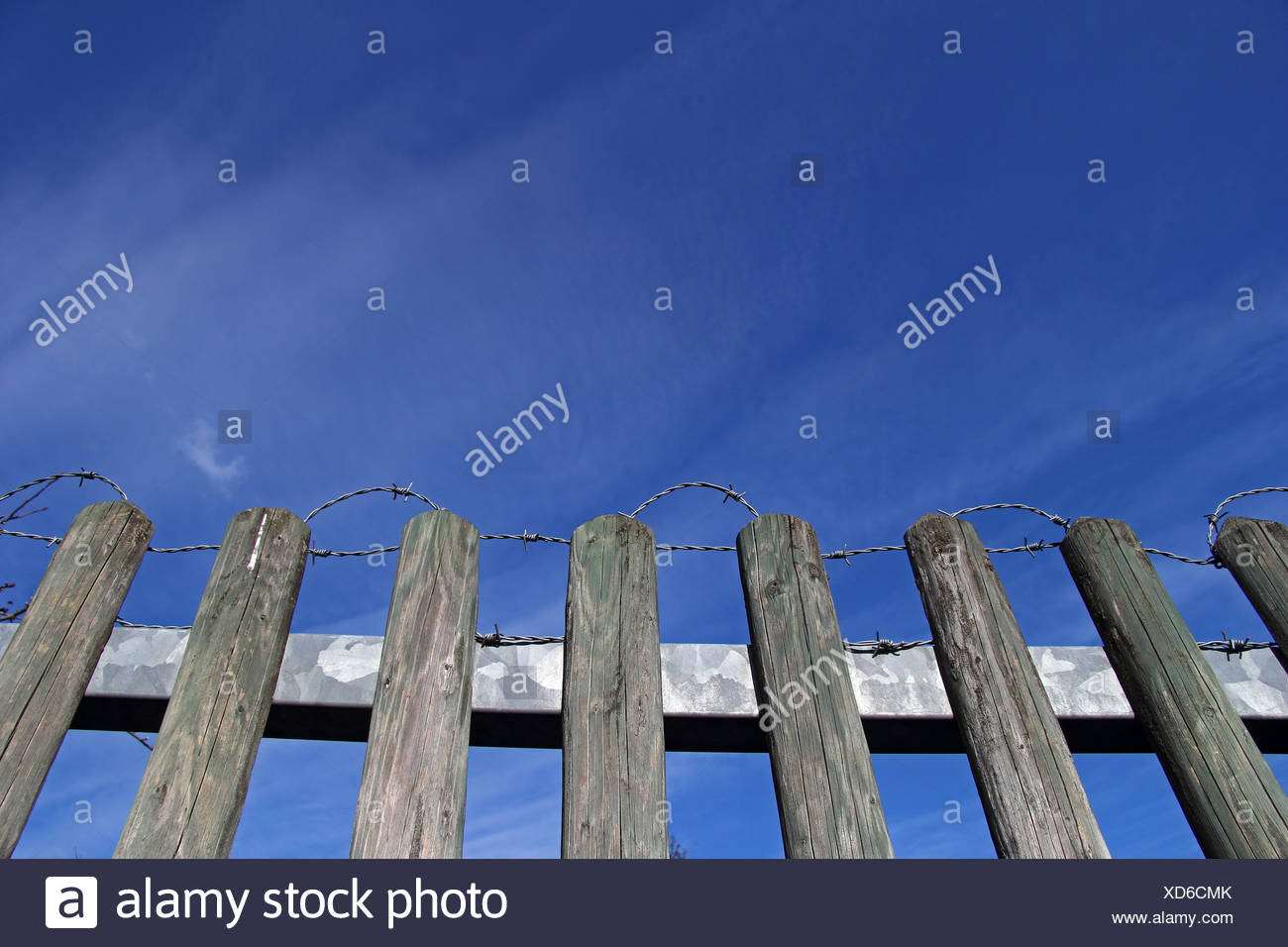 Wooden fence with barbed wire, against a blue sky - Stock Image