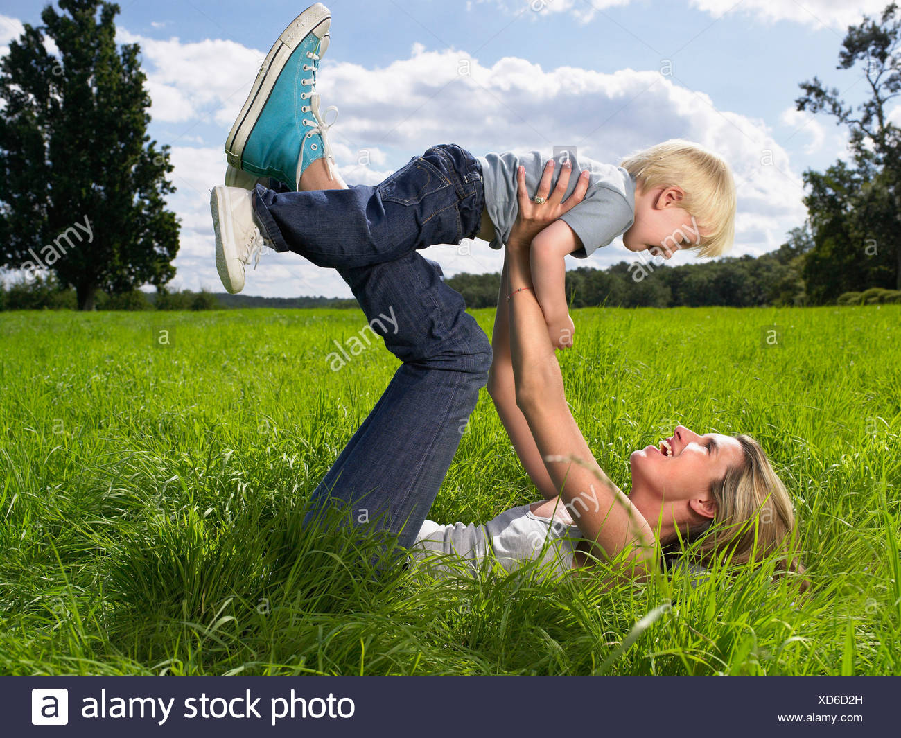 Mother and son playing in a field. - Stock Image