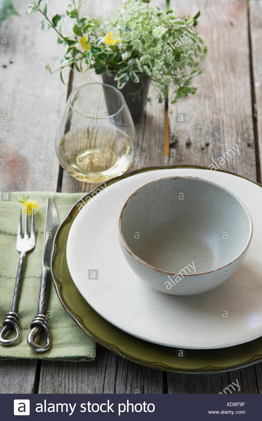 Place setting and wine on rustic wood table - Stock Image