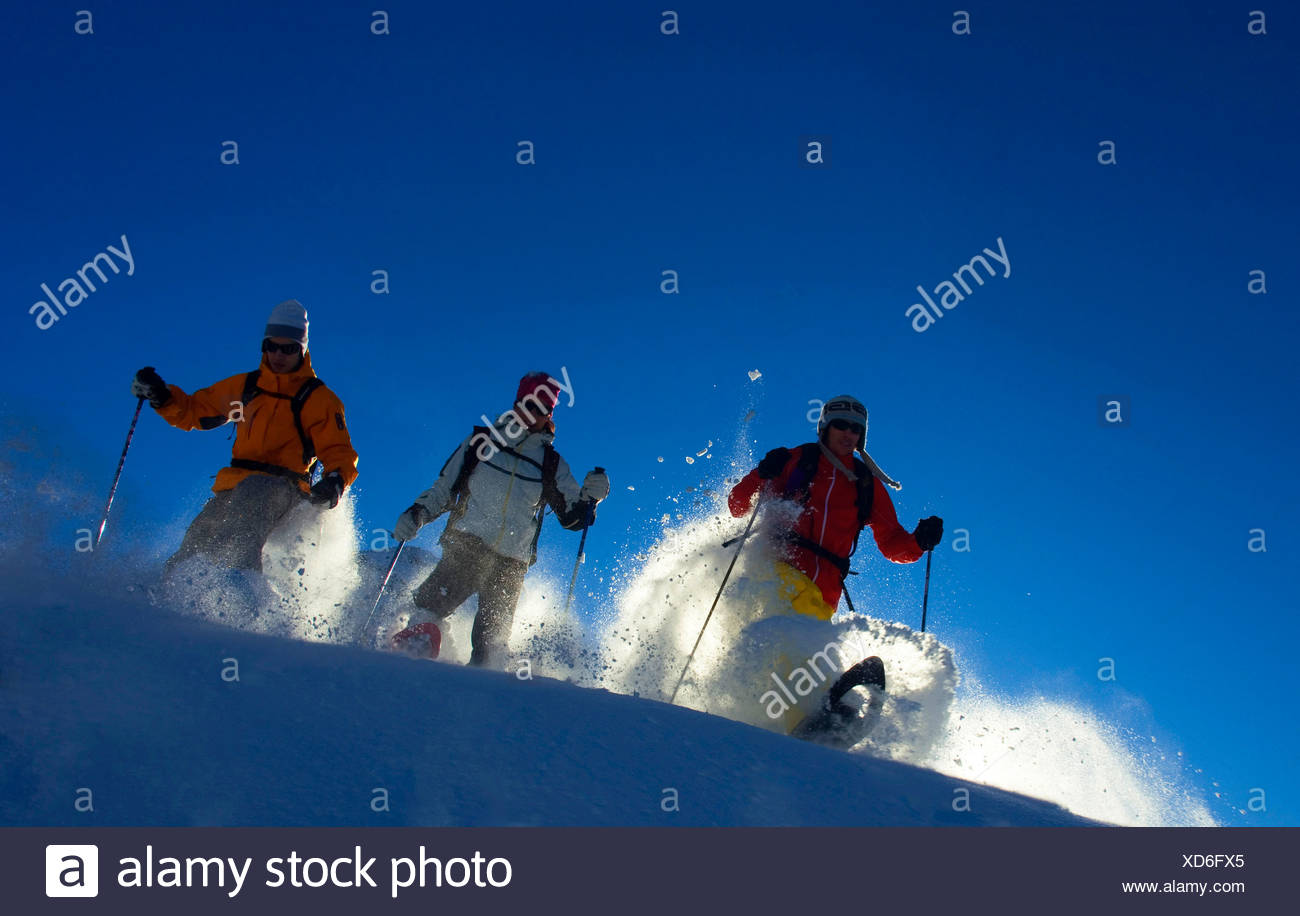 three persons on snow shoes, walking in deep powder snow, France, Alps Stock Photo