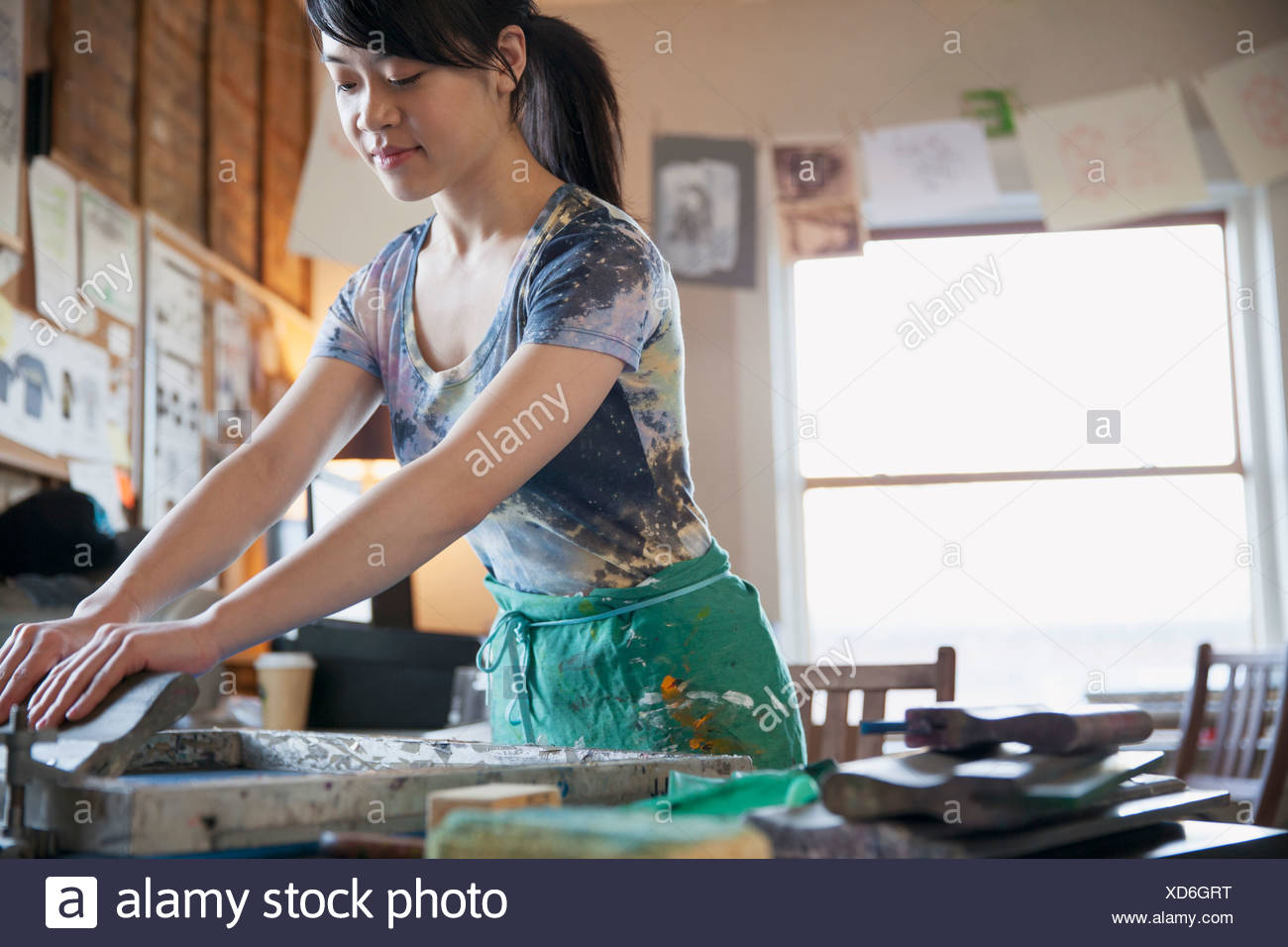 Female design professional working on silk screen at workshop - Stock Image