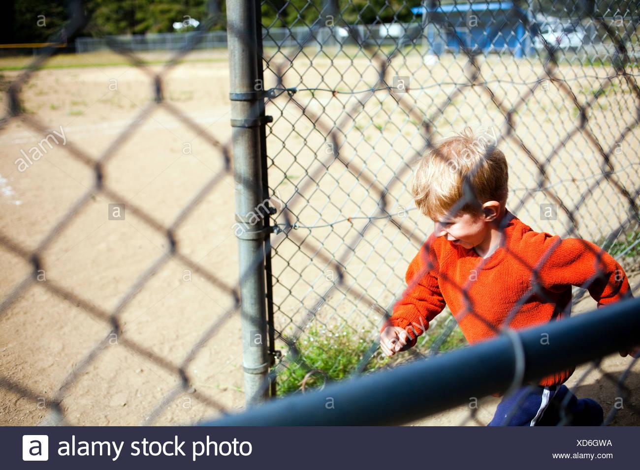 Young boy running onto baseball field - Stock Image