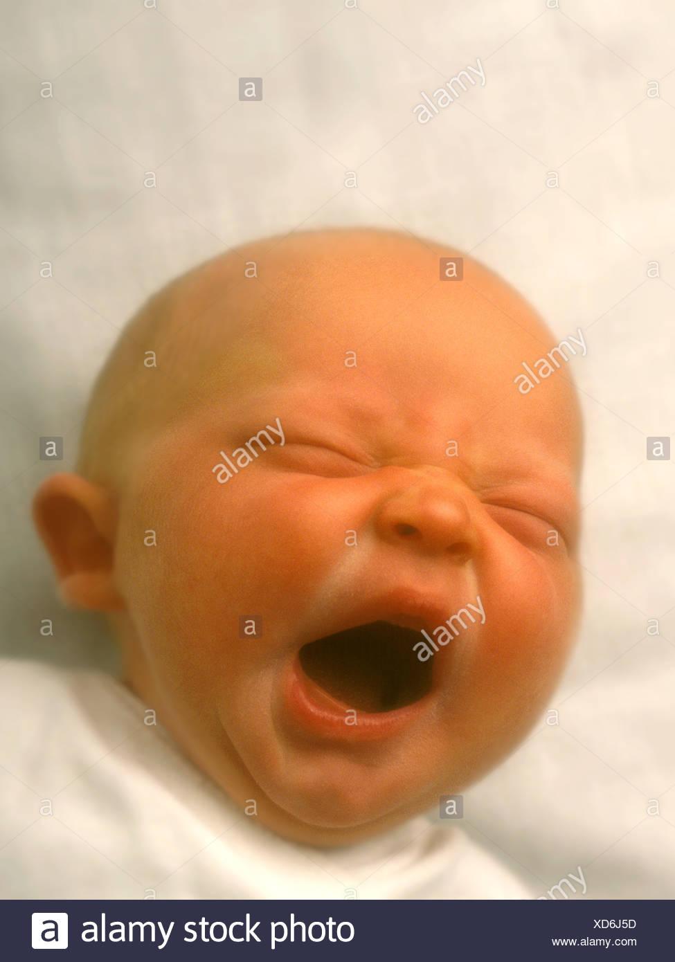 Newborn infant yawning and lying on white blanket - Stock Image
