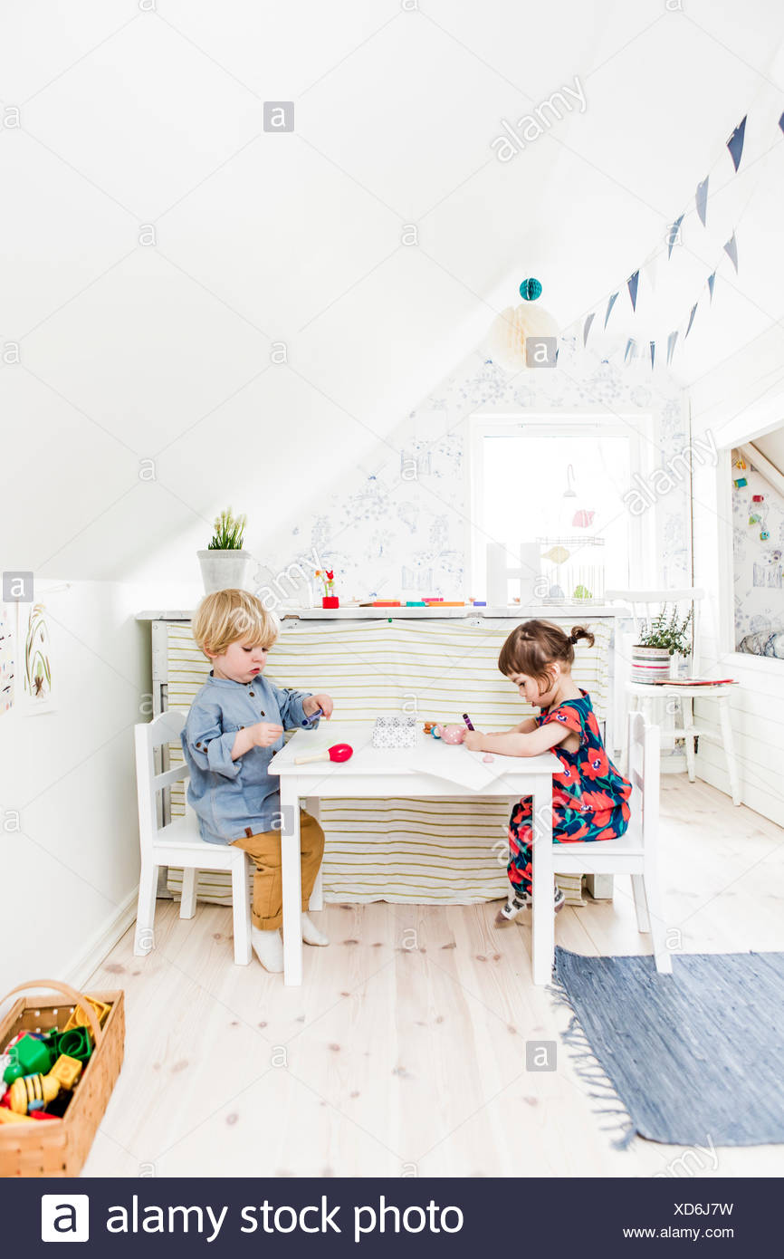 Sweden, Boy and girl (2-3) playing in bedroom - Stock Image