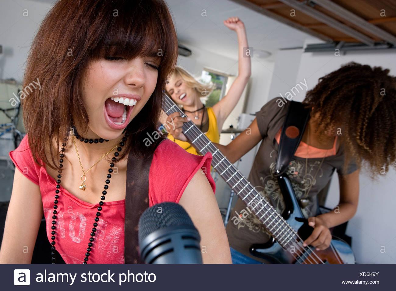 Three teenage girls  in garage band, teenage girl singing in foreground - Stock Image