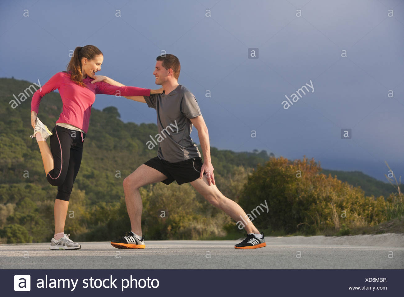 Young athletic couple stretching - Stock Image