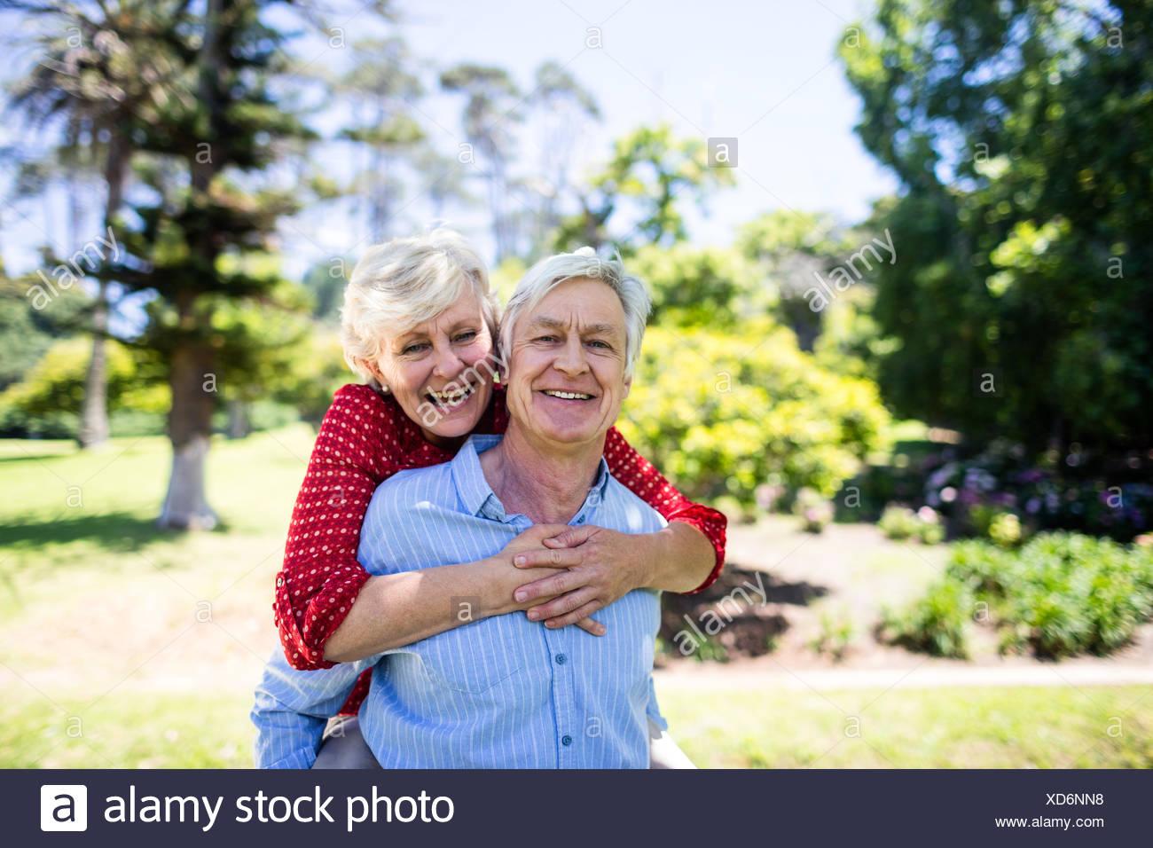 Happy senior man giving a piggy back to senior woman - Stock Image