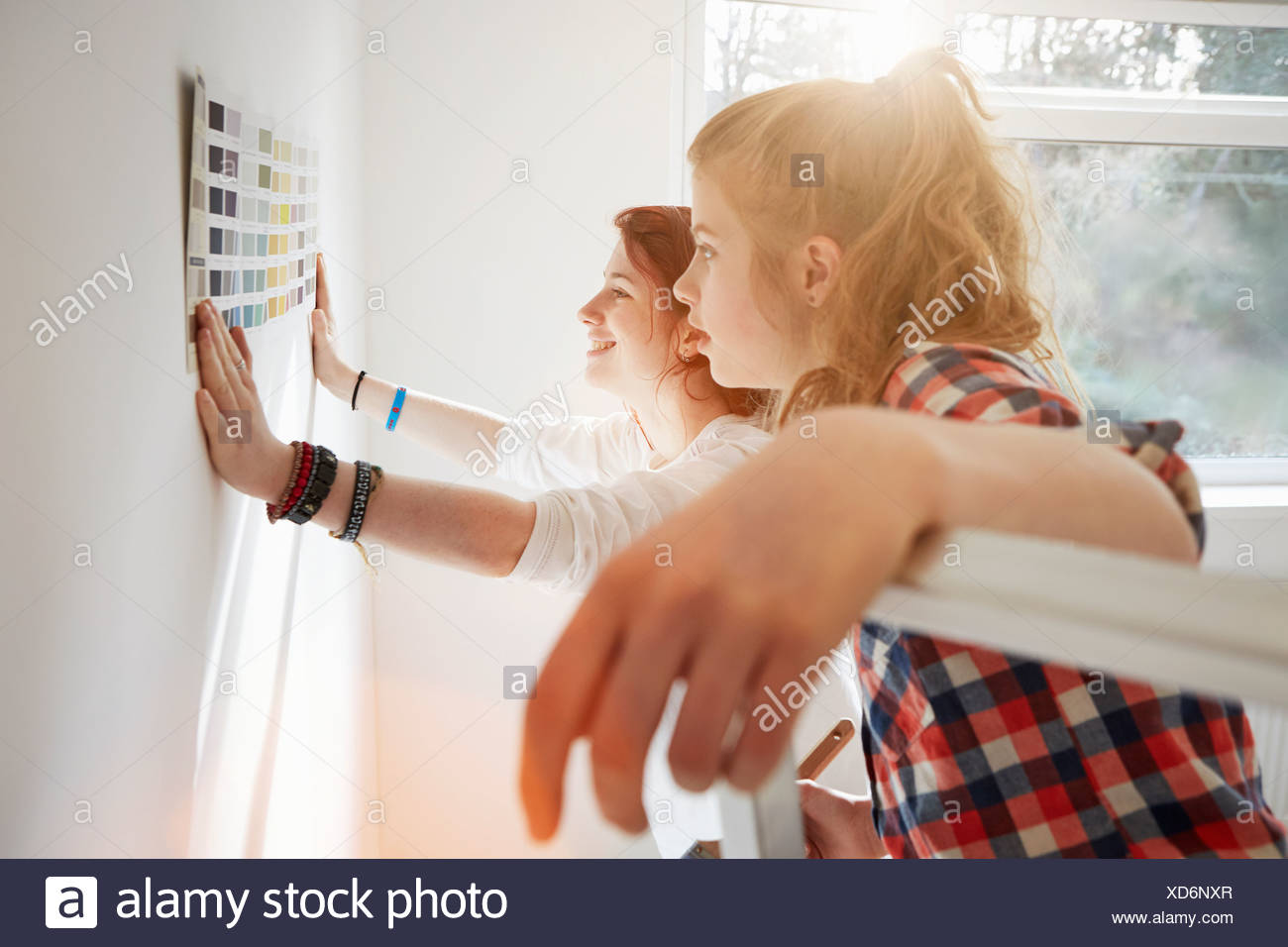 Teenage sisters holding color swatch against wall - Stock Image