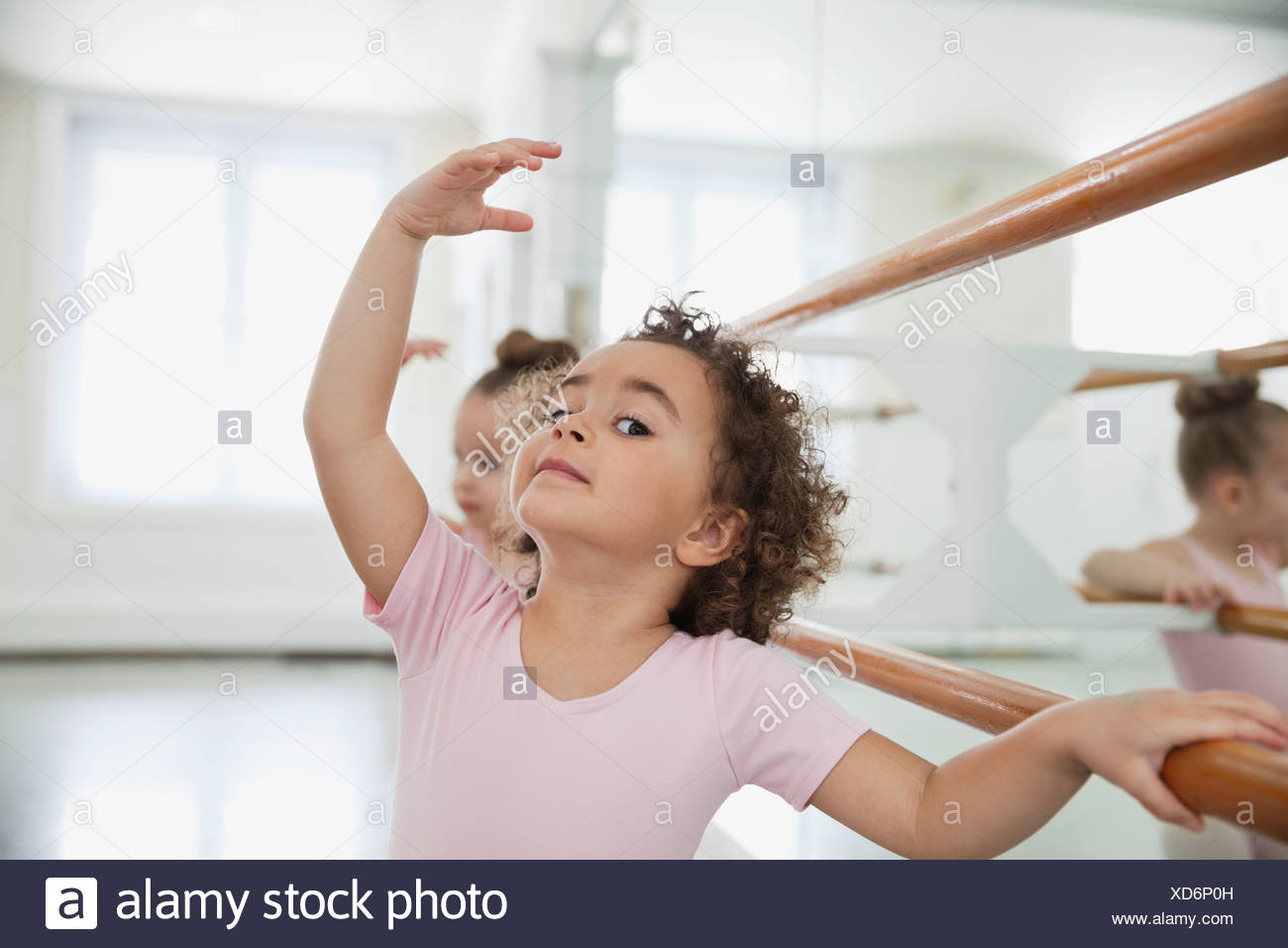 Portrait of girl practicing ballet with friend in ballet studio - Stock Image