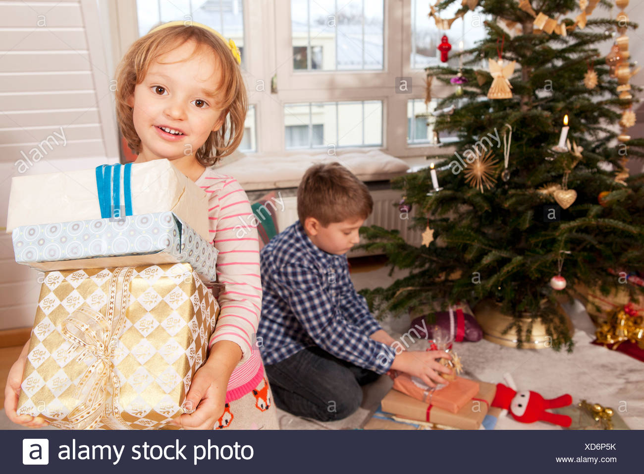 Little girl holding gift boxes, brother in background, Munich, Bavaria, Germany Stock Photo