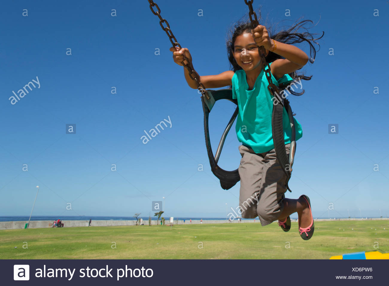 Smiling girl swinging on swing - Stock Image