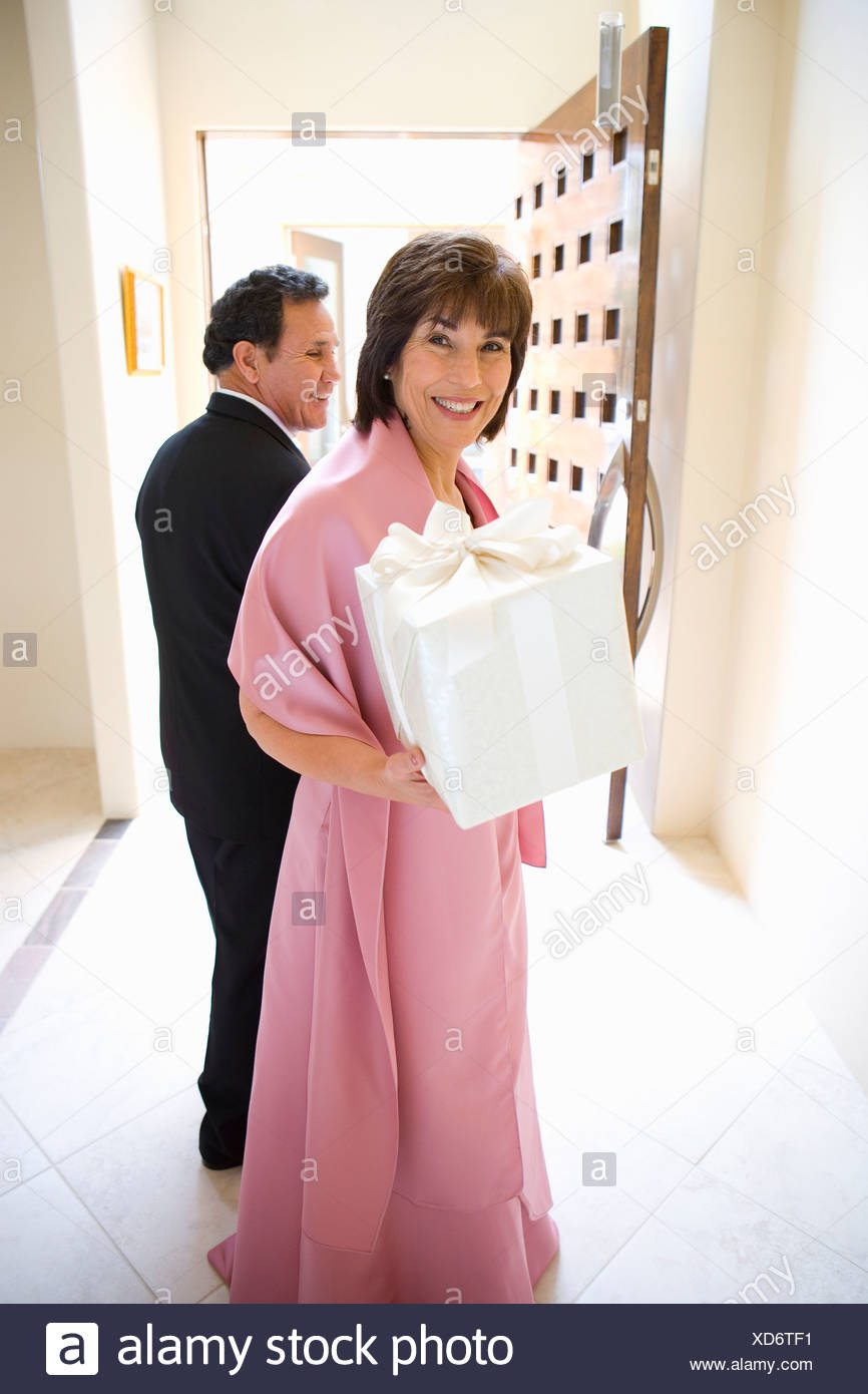 Senior couple, in formalwear, standing in hallway, woman carrying wedding gift, smiling, portrait - Stock Image
