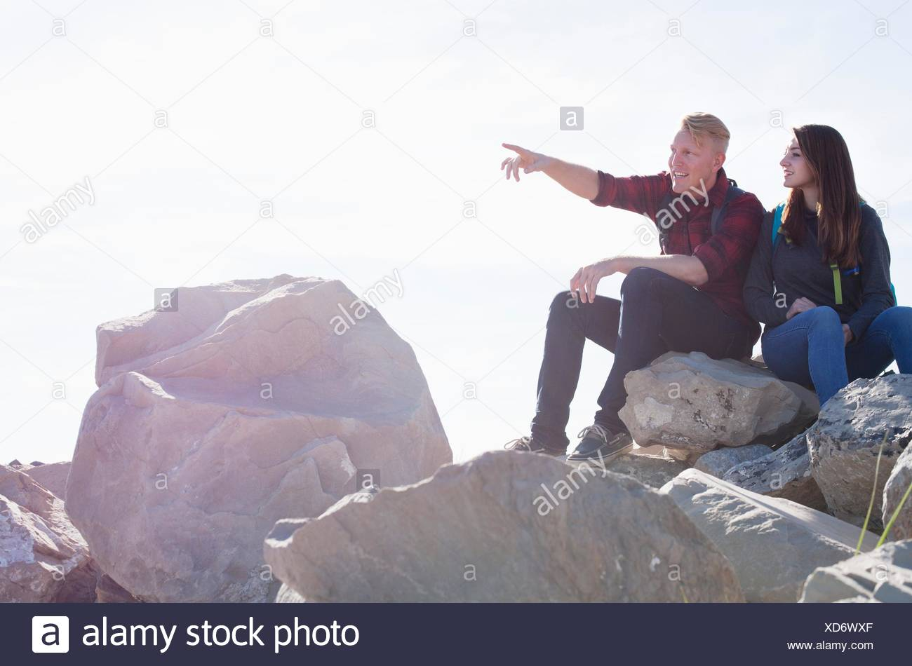 Young couple sitting on rocks looking away pointing - Stock Image