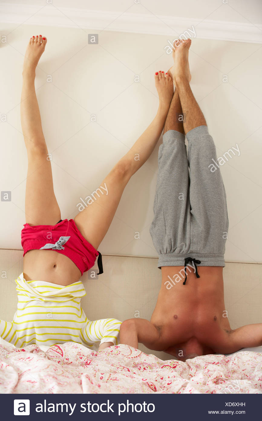 Couple Standing On Head In Bed - Stock Image
