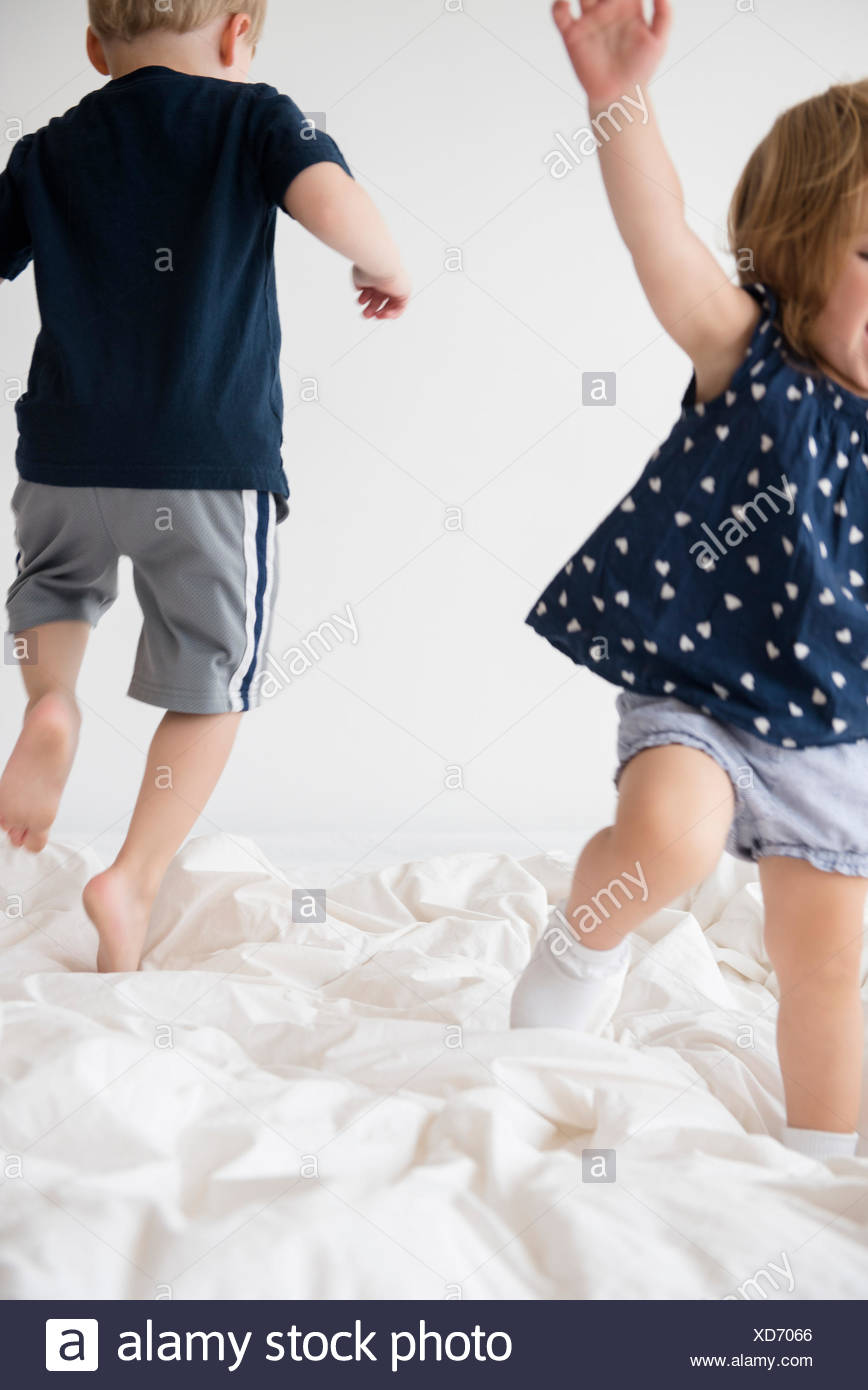 Brother (2-3) with sister (2-3) jumping on bed - Stock Image