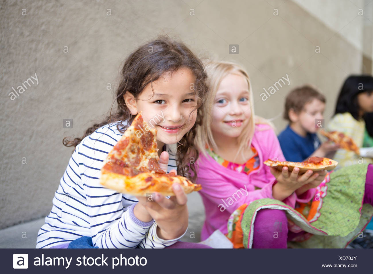 Small group of children eating pizza outdoors - Stock Image