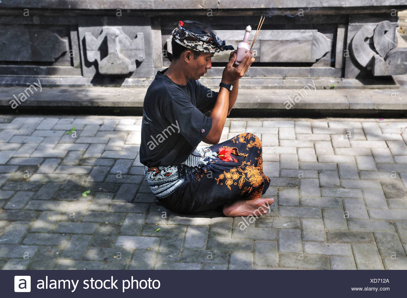 Young man bringing offerings to the gods, Denpasar, Bali, Indonesia, Southeast Asia - Stock Image