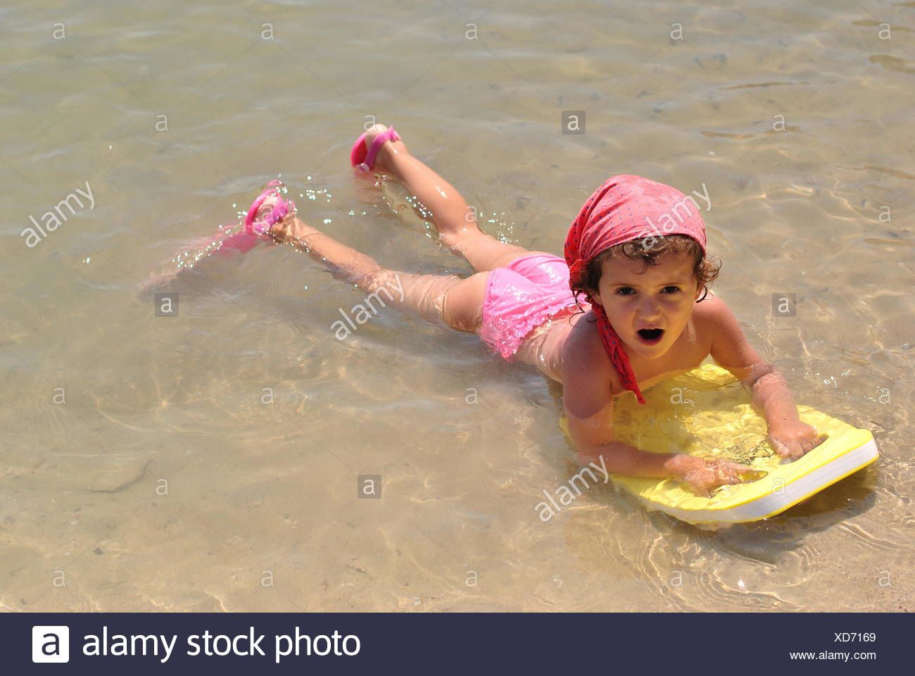 Girl lying in shallows on the beach with her kick board and diving flippers Stock Photo