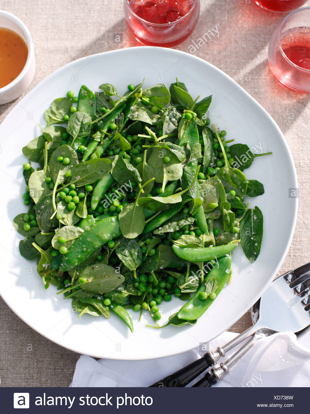 Plates of salad with peas and baby spinach - Stock Image